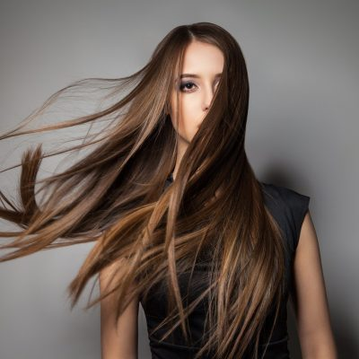 Portrait of calm emotionless model with long windy hair.Studio shot.